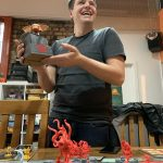 Winner of Cthulhu Wars tournament holding trophy
